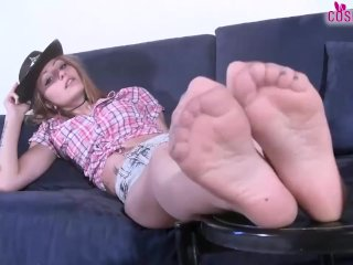 Redhead cowgirl in pantyhose gives herself a foot massage